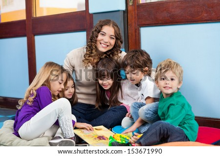 Happy teacher sitting with children on floor in classroom - stock photo