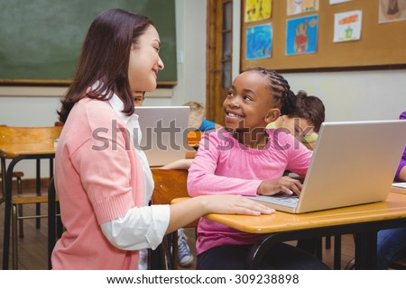 Happy teacher using laptop with student at the elementary school - stock photo