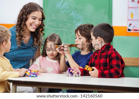 Happy teacher with children playing musical instruments in classroom