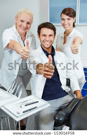 Happy team at dentist holding their thumbs up in dental practice - stock photo