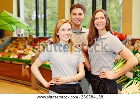 Happy team in supermarket with store manager and two salespeople - stock photo