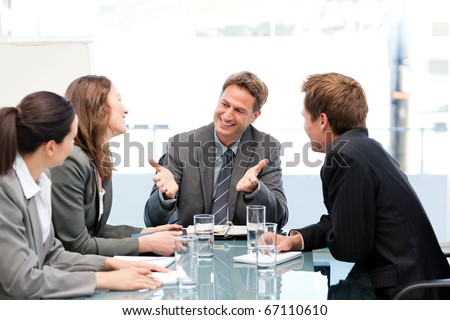Happy team laughing together at a meeting in the office - stock photo