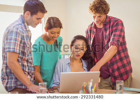 Happy team looking at their work on a computer in the office - stock photo