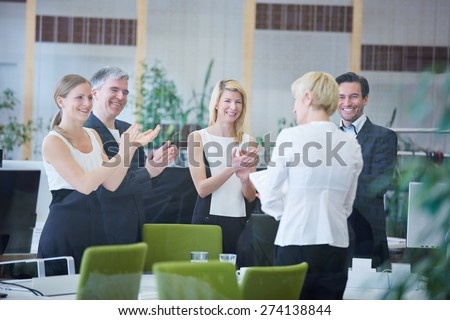 Happy team of business people in office giving applause - stock photo