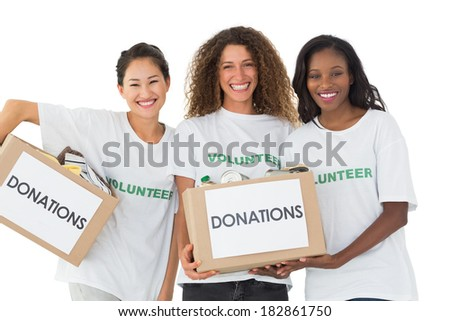 Happy team of volunteers smiling at camera holding donations boxes on white background