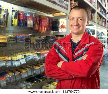 Happy technical adviser in tools shop - stock photo
