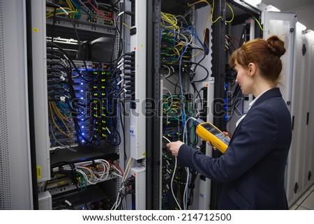 Happy technician using digital cable analyzer on server in large data center