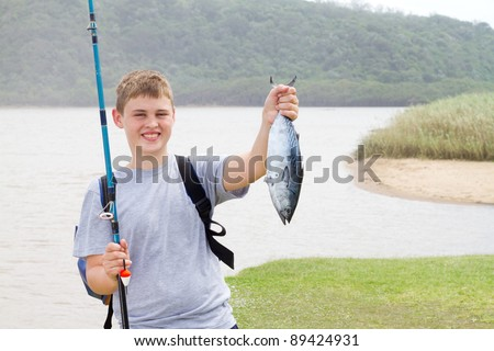 happy teen boy showing a fishing he just caught - stock photo