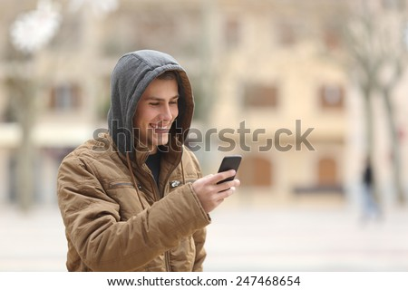 Happy teen boy walking on the street and using a smart phone - stock photo