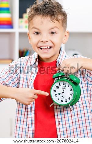 Happy teen boy with alarm clock in school classroom - stock photo