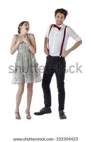 Happy teen couple dressed up in prom clothes stand together and laugh. Vertical, isolated on white, copy space.