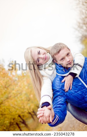 Happy teen couple having fun outdoors on cold autumn day - stock photo