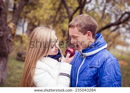 Happy teen couple outdoors on cold autumn day sharing apple - stock photo