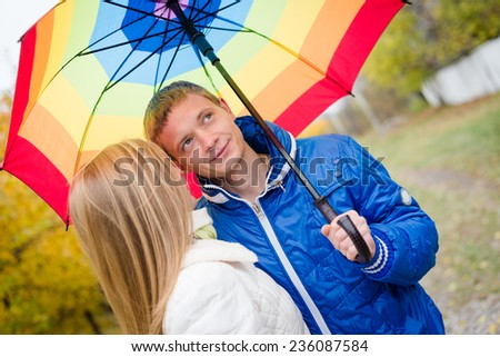 Happy teen couple walking outdoors on cold autumn day under bright umbrella - stock photo