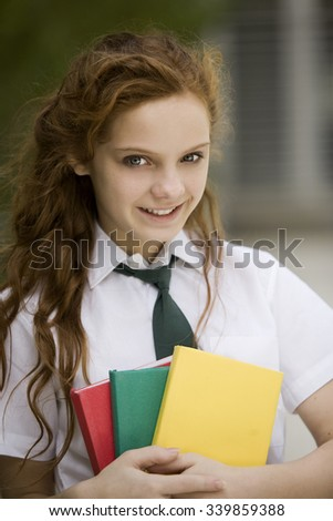 Happy teen female student with books