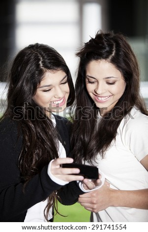 Happy teen friends with mobile phone - stock photo