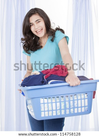 Happy teen girl doing the laundry, carrying a load of clothes in basket - stock photo