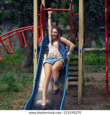 Happy teen girl has fun  on child hillock on playground. Outdoors. Image toned and noise added. - stock photo