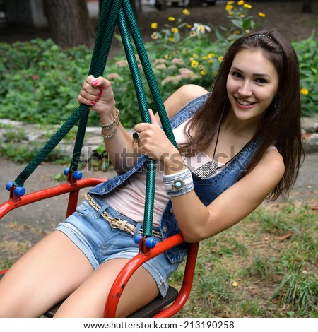 Happy teen girl has fun on swing on playground. Outdoors. Image toned and noise added. - stock photo