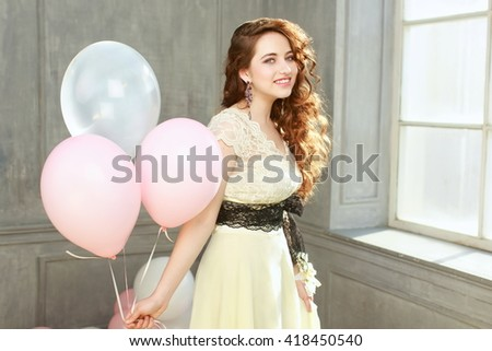 Happy teen girl in prom look with helium air balloons - stock photo