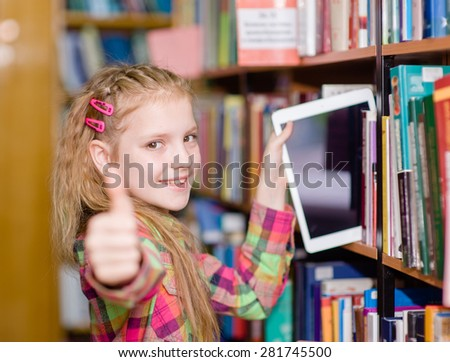 Happy teen girl pulls a tablet pc off the shelves in the library and showing thumb up - stock photo