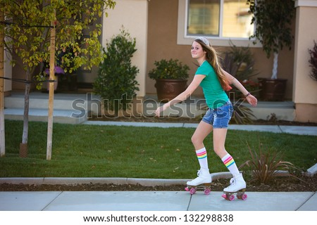 Happy teen girl roller skating in front of her house - stock photo