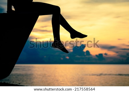 happy teen girl sitting on beach at the dawn time - stock photo
