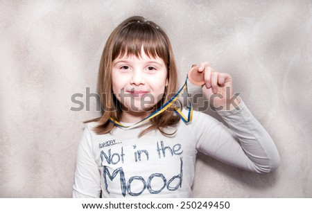 Happy teen girl stands with medal in hand