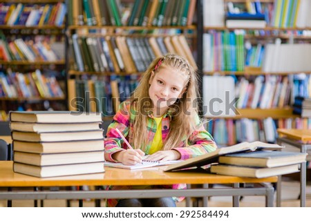 Happy teen girl studying in the library - stock photo