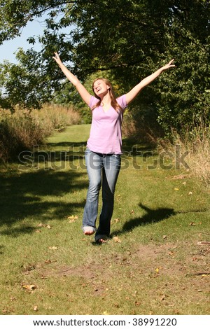 happy teen girl walking on outdoor path - stock photo