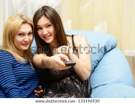 Happy teen girl watching tv together with her mother on sofa at home - stock photo