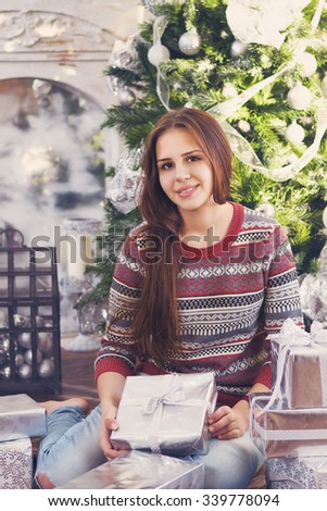 Happy teen girl with Christmas present in her hands by the Christmas tree - stock photo