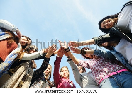 Happy teen girls having good fun time outdoors and posing in circle with copy space