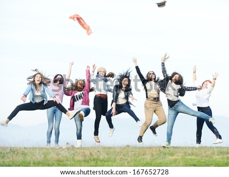 Happy teen girls having good fun time outdoors jumping up in air - stock photo