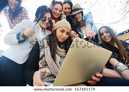 Happy teen girls having good fun time outdoors using laptop - stock photo