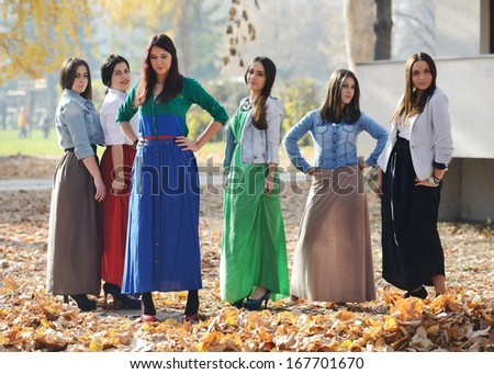 Happy teen girls having good fun time outdoors wearing party dresses
