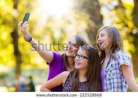 Happy teen girls taking selfie in park with mobile phone - stock photo