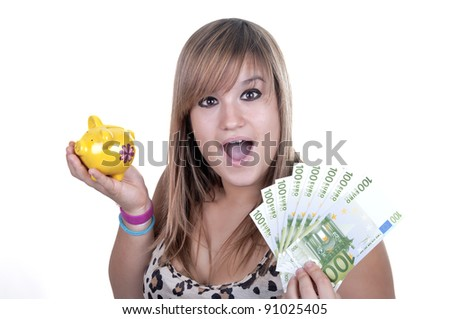 Happy teen holding a piggy bank and bills, isolated on white background - stock photo