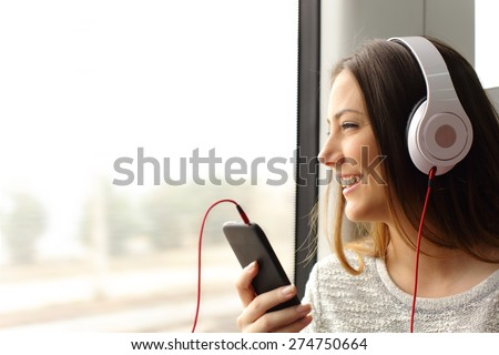 Happy teen passenger listening to the music traveling in a train and looking through the window - stock photo