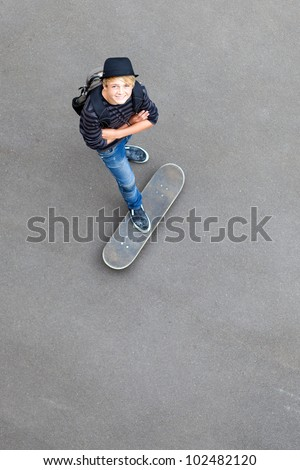 happy teen skateboarder standing on skateboard and looking up - stock photo