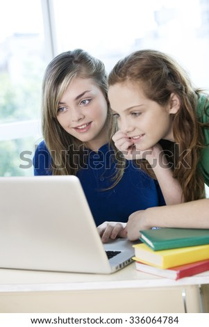 Happy teen students with computer - stock photo