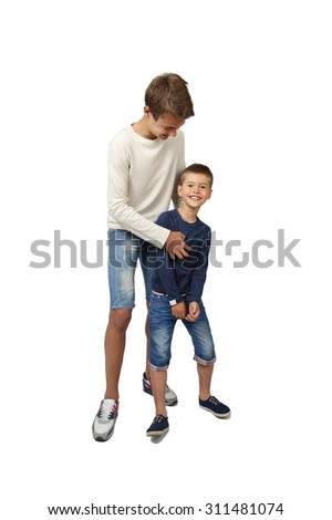 Happy teenage boy plays with his joyful little brother isolated on white background - stock photo