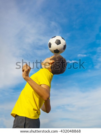 happy teenage boy with a soccer ball on his head on blue sky background