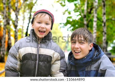 happy teenage brothers portrait in the autumn park - stock photo