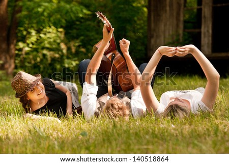 Happy teenage friends relax with guitar music on the green meadow - stock photo
