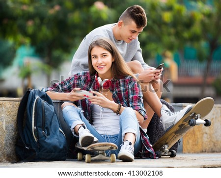 Happy teenage friends relaxing with mobile phones in sunny day  - stock photo