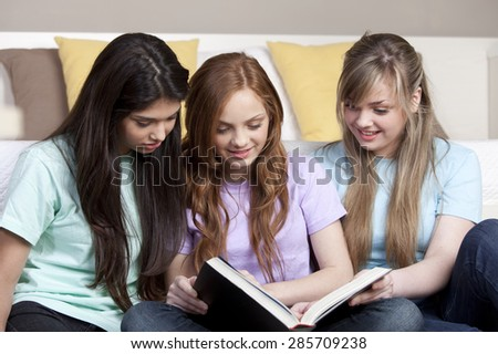 Happy teenage friends studying with book - stock photo