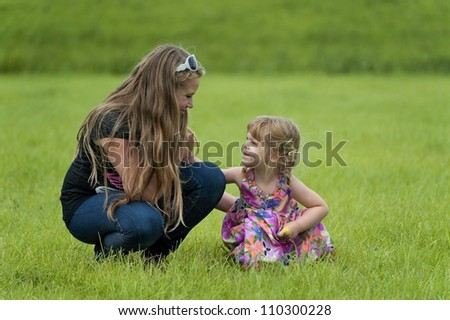 Happy teenage girl and a toddler in the grass - stock photo