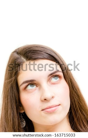 Happy teenage girl headshot looking up on copyspace over white background