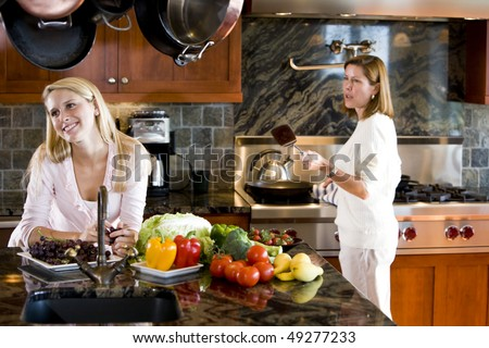 Happy teenage girl in kitchen smiling with mother talking - stock photo